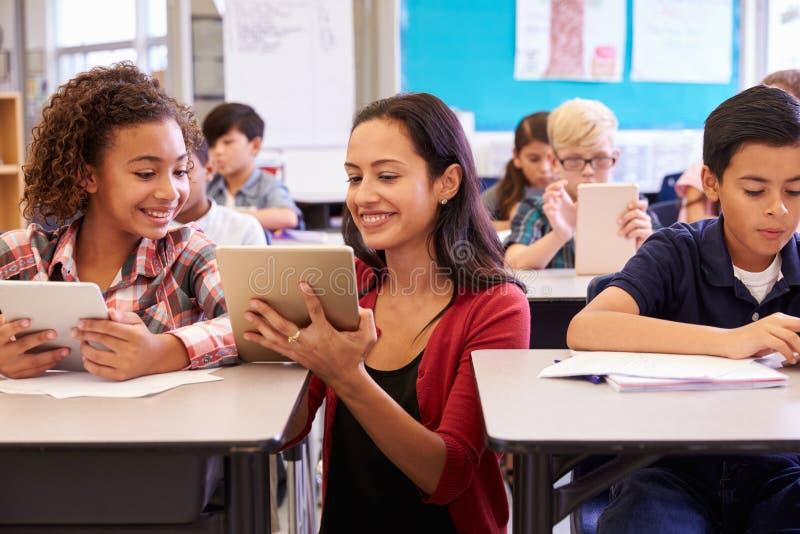 Leraar die jonge geitjes met computers in basisschool helpen stock foto's