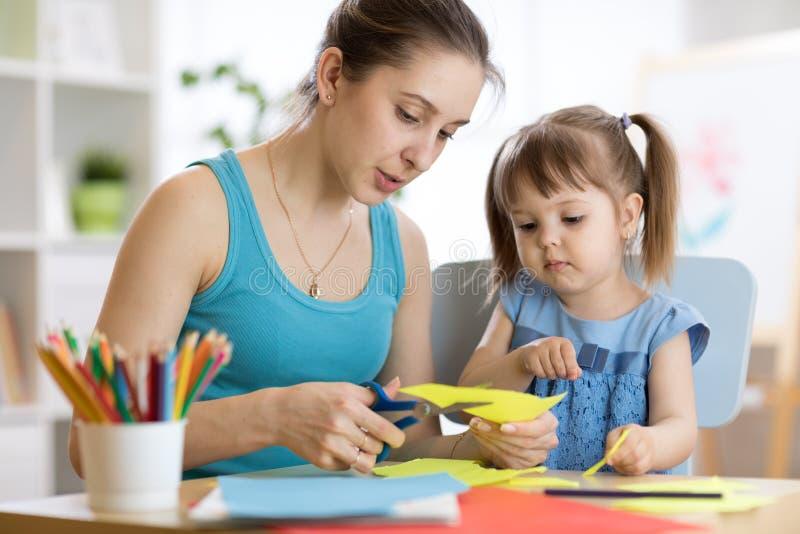 Leraar die kind helpen om gekleurd document te werken stock afbeelding