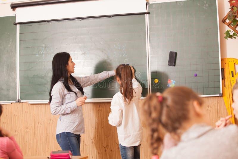 Leraar die leerling helpen bij bord stock foto's