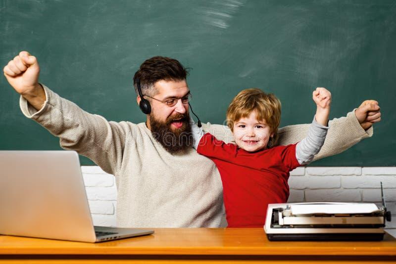 Leraar die leerlingen helpen die op bureaus in klaslokaal bestuderen Peuterleerling Jongelui of volwassene Leraar en jong geitje  royalty-vrije stock foto