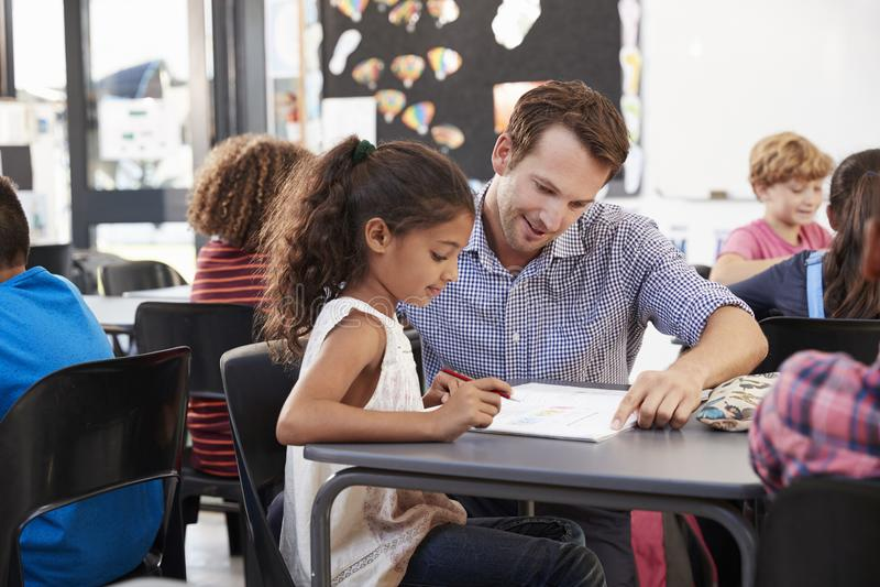 Leraar die met jong schoolmeisje bij haar bureau in klasse werken stock afbeeldingen