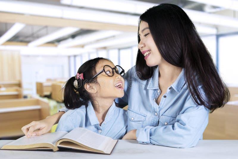 Leraar die met student spreken terwijl het onderwijzen stock afbeelding