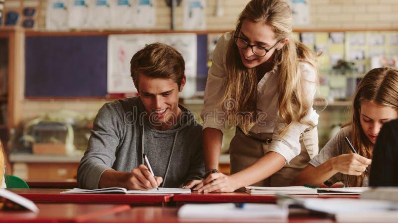 Leraar die student helpen tijdens haar klasse stock fotografie