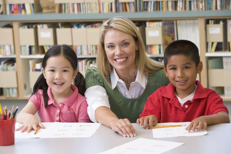 Leraar die studenten helpt het schrijven vaardigheden leren stock afbeeldingen