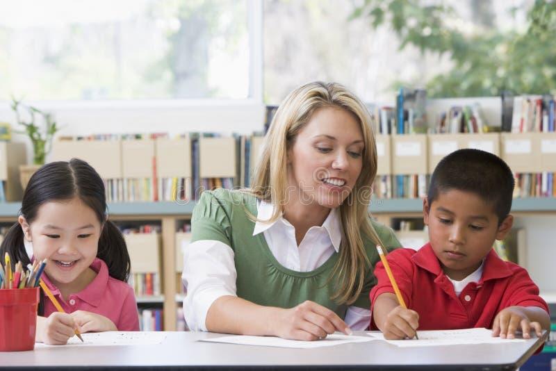 Leraar die studenten met het schrijven van vaardigheden helpt royalty-vrije stock foto's