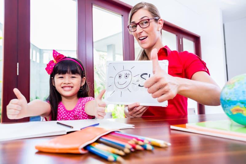 Leraar die taallessen geven aan Chinees kind stock afbeeldingen