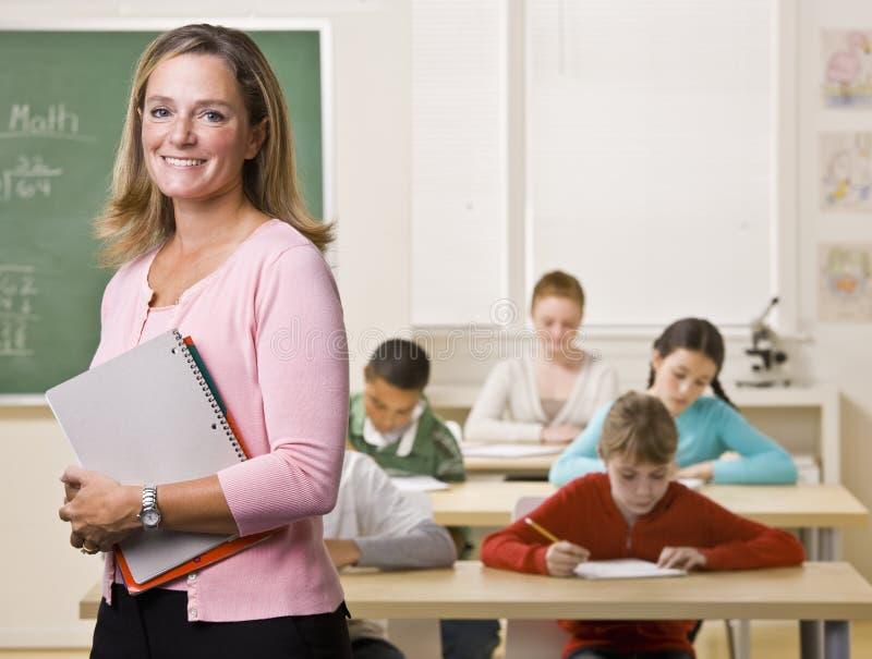 Leraar die zich met notitieboekje in klaslokaal bevindt stock fotografie
