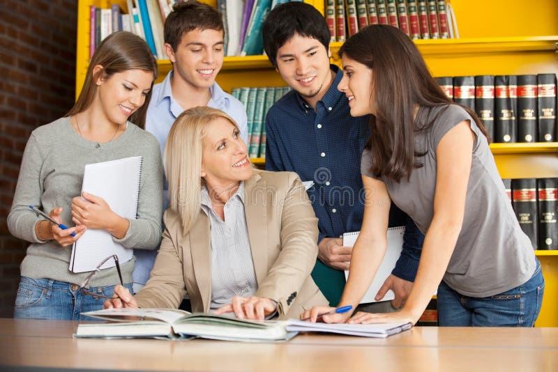 Leraar Discussing With Students bij Lijst binnen royalty-vrije stock afbeeldingen
