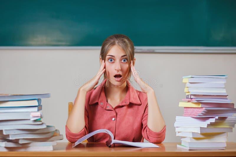 Leraar door boeken wordt omringd die in schoolklaslokaal dat zitten Emotionele leraar bij de lijst De ruimte van het exemplaar Gr stock afbeelding
