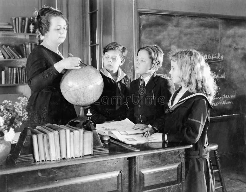 Leraar in een klaslokaal met drie leerlingen die aan een bol richten (Alle afgeschilderde personen leven niet langer en geen land stock afbeeldingen