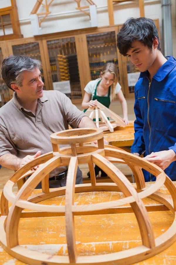 Leraar en een student in een houtbewerkingsklasse die aan een kader werken royalty-vrije stock fotografie