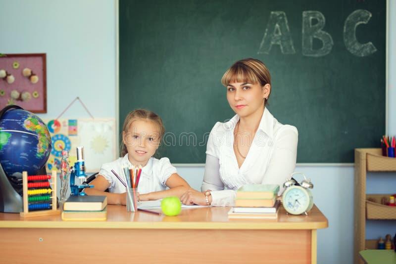 Leraar en haar studenten in klaslokaal Leraar die schoolmeisje met haar thuiswerk in klaslokaal helpen op school stock afbeelding