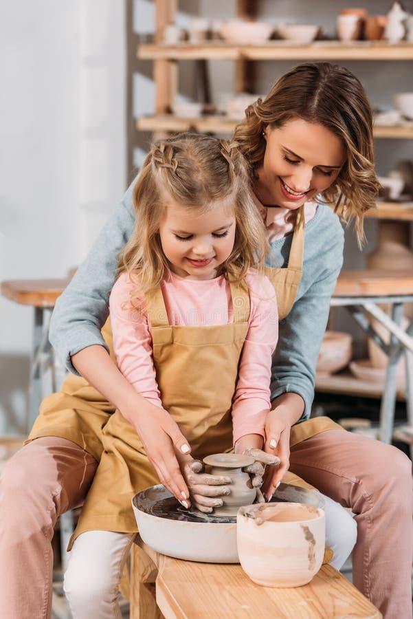 leraar en jong geitje die ceramische pot samen maken stock fotografie