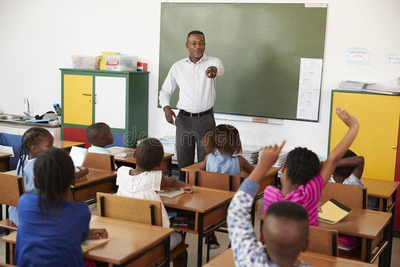 Leraar en jonge geitjes met handen omhoog in een basisschoolklasse stock fotografie