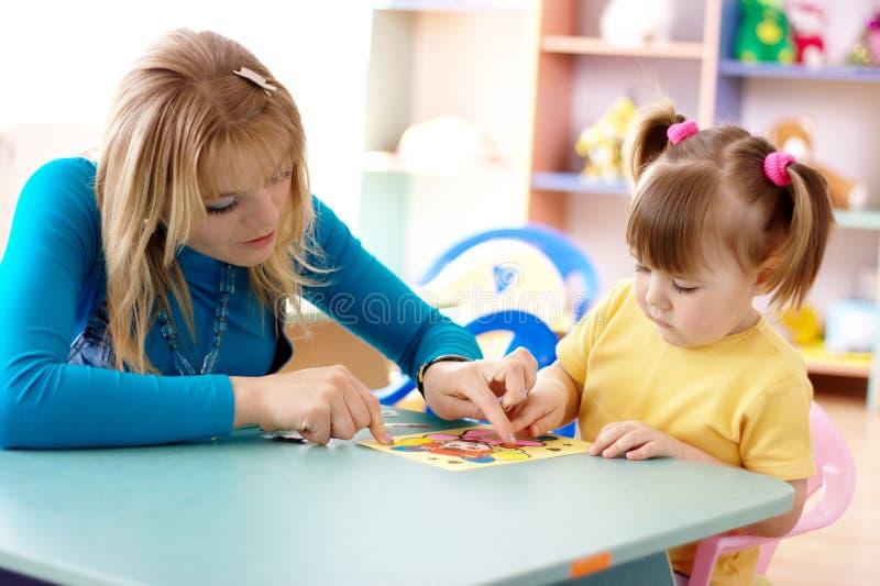 Leraar en kind in kleuterschool stock afbeeldingen