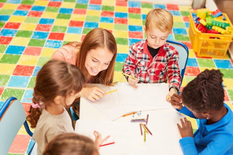Leraar en kinderen samen in de tekeningscursus royalty-vrije stock foto