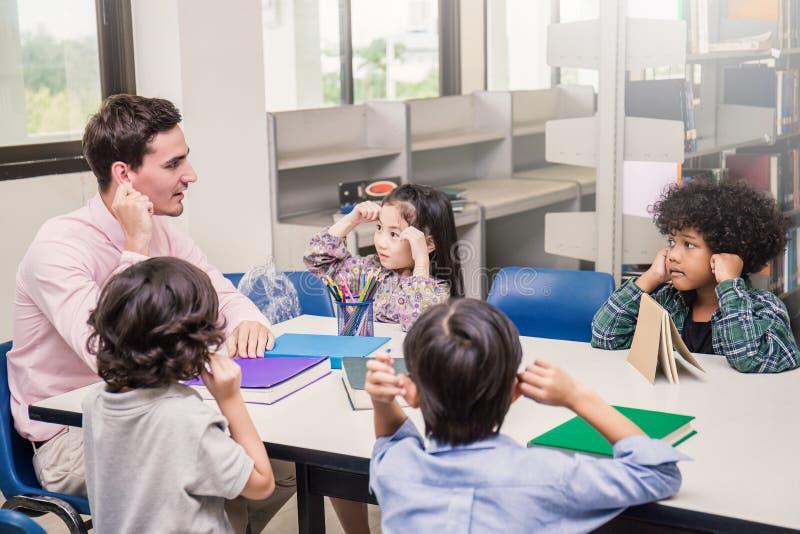 Leraar en kleine kinderen die handen wat betreft hun oren zitten stock afbeeldingen