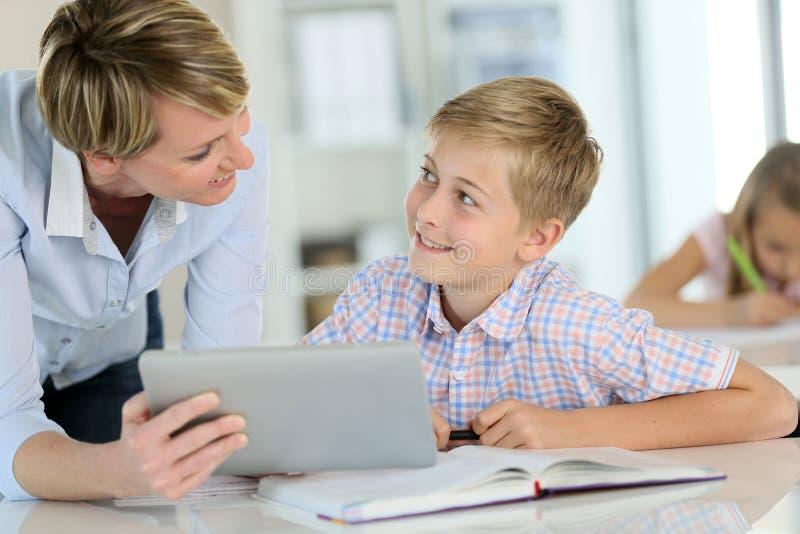 Leraar en leerlingen die tablet gebruiken op school stock afbeeldingen