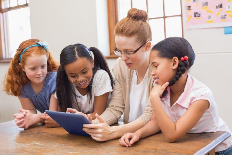Leraar en leerlingen die tabletcomputer bekijken royalty-vrije stock foto's