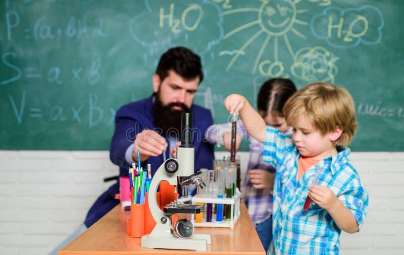 Leraar en leerlingen met reageerbuizen in klaslokaal Interessante schoolklassen Schoolonderwijs Schoolchemie stock afbeeldingen
