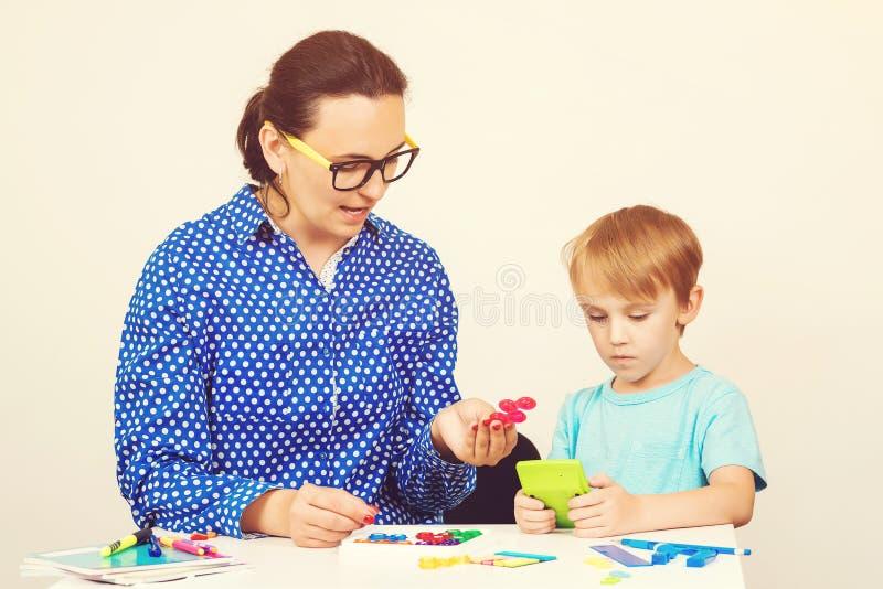Leraar en leuk weinig jongen die pret hebben, die logisch spel spelen Jong geitje met leraar het leren bij peuterklaslokaal Leraa stock afbeeldingen