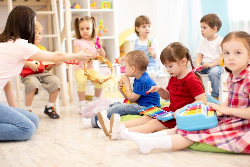 Leraar en leuke jonge geitjes tijdens muziekles in kleuterschool royalty-vrije stock fotografie