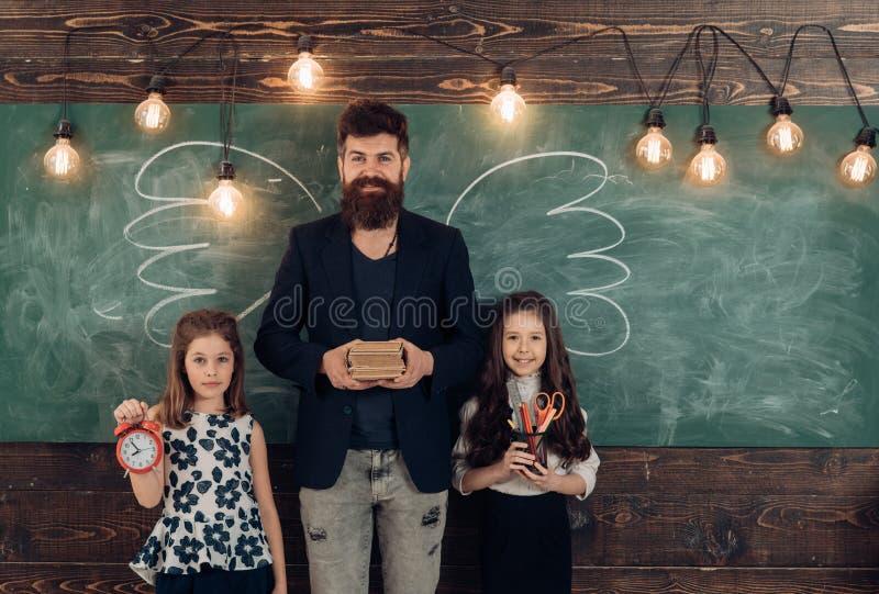 Leraar en meisjesleerlingen in klaslokaal, bord op achtergrond Kinderen en leraar met getrokken door krijtvleugels Mens stock afbeeldingen