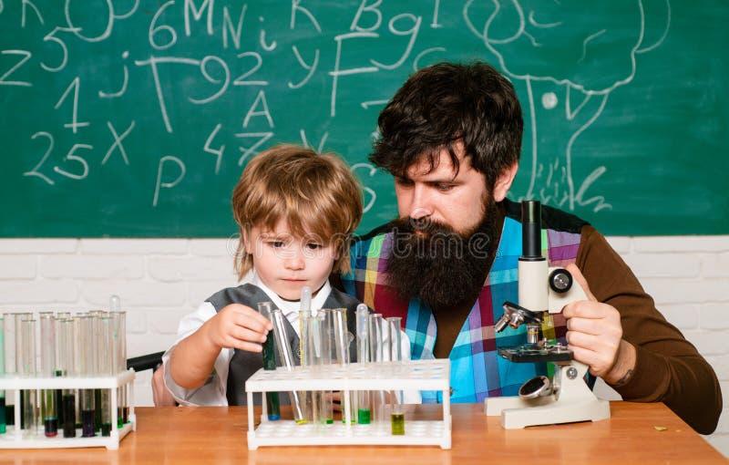 Leraar en schooljongen die microscoop in klasse gebruiken wunderkind Wetenschap en onderwijsconcept Thuis het leren Concept van royalty-vrije stock foto's