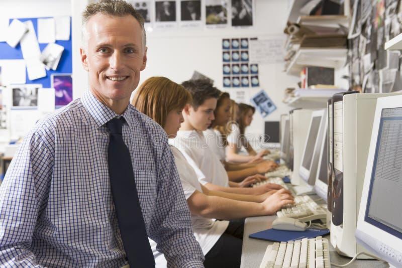 Leraar en schoolkinderen die op computers bestuderen royalty-vrije stock afbeeldingen