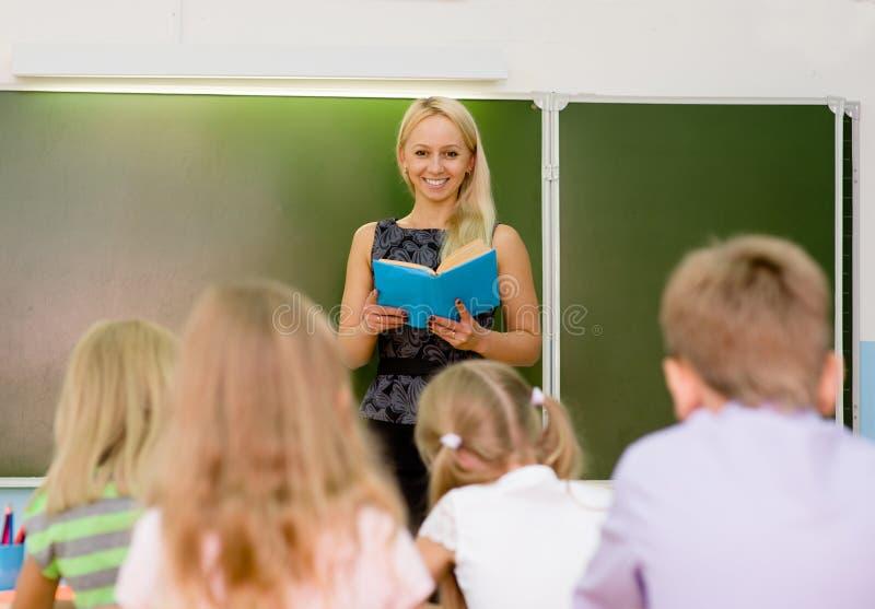 Leraar en schoolkinderen in klaslokaal bij les stock fotografie