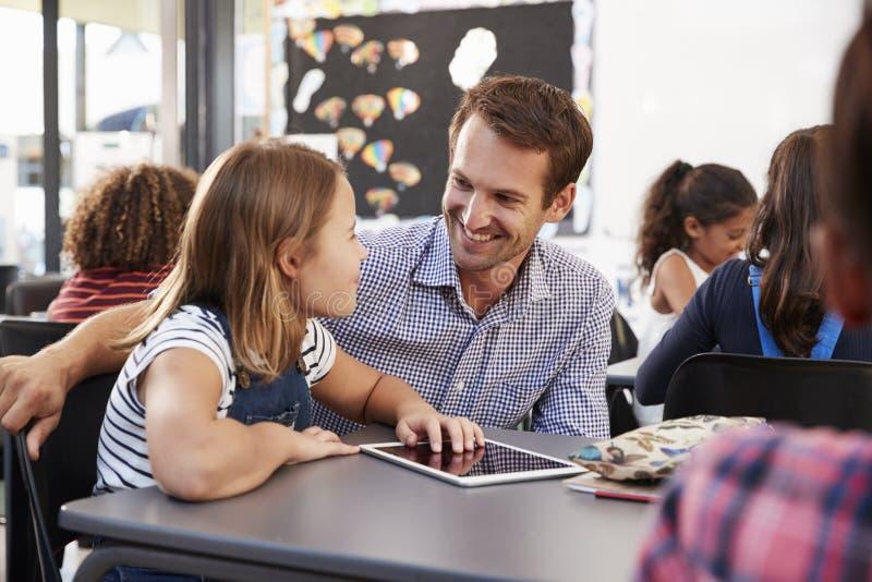 Leraar en schoolmeisje die tablet gebruiken die elkaar bekijken royalty-vrije stock foto