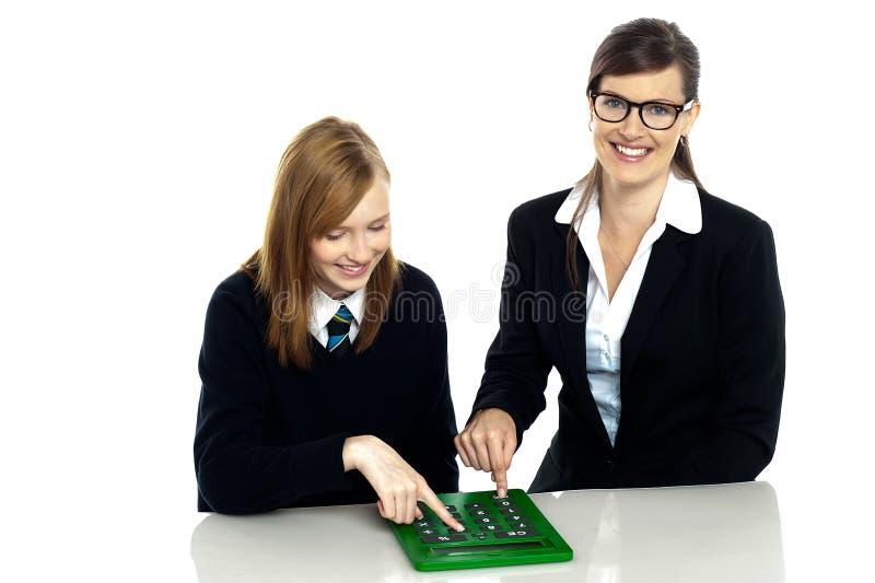 Leraar en student die aan calculator werken royalty-vrije stock afbeeldingen