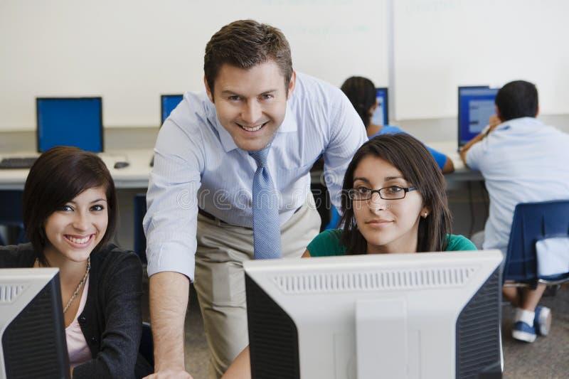 Leraar en Studenten in Computerlaboratorium stock foto's