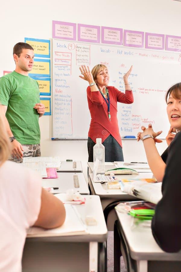 Leraar en studenten die een gesprek met elkaar hebben stock afbeeldingen