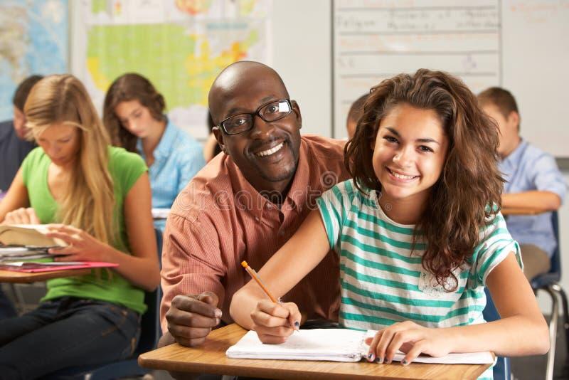 Leraar Helping Female Pupil die bij Bureau in Klaslokaal bestuderen royalty-vrije stock afbeeldingen