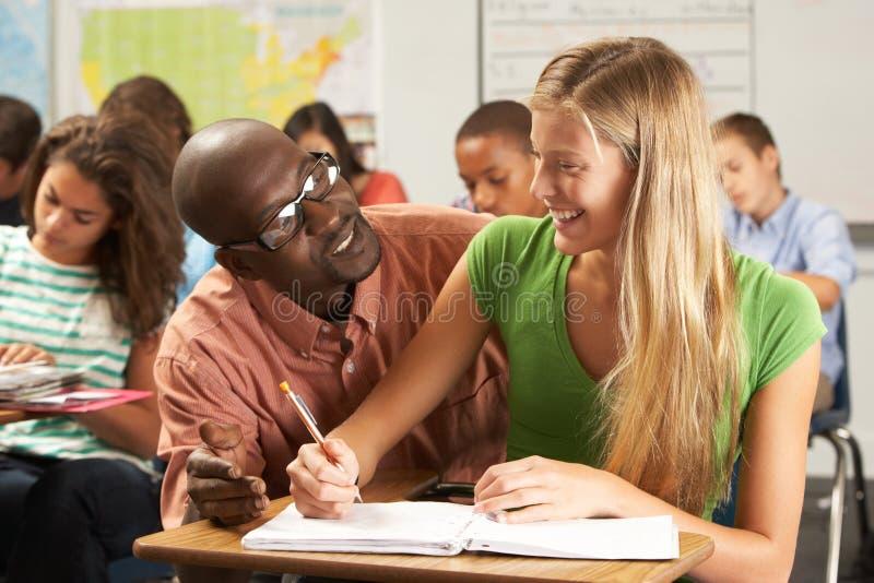 Leraar Helping Female Pupil die bij Bureau in Klaslokaal bestuderen royalty-vrije stock afbeelding
