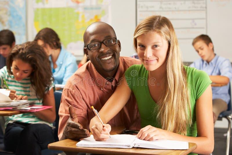 Leraar Helping Female Pupil die bij Bureau in Klaslokaal bestuderen stock afbeelding