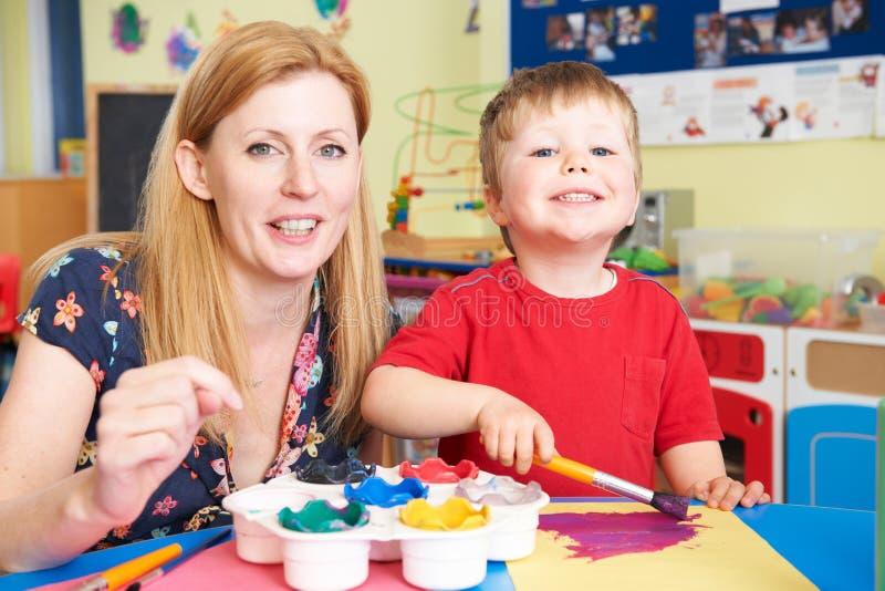 Leraar Helping Preschool Child in Art Class stock foto