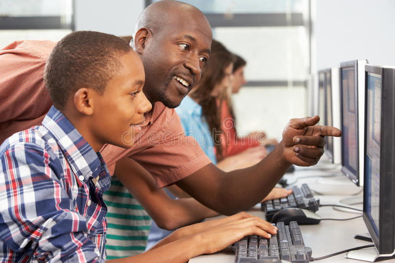Leraar Helping Students Working bij Computers in Klaslokaal stock foto's