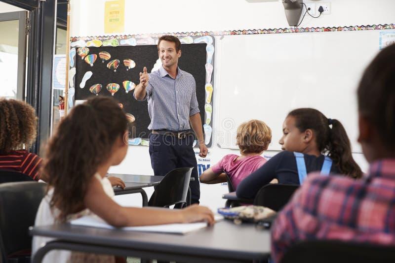Leraar het gesturing aan klasse in een basisschoolles royalty-vrije stock foto