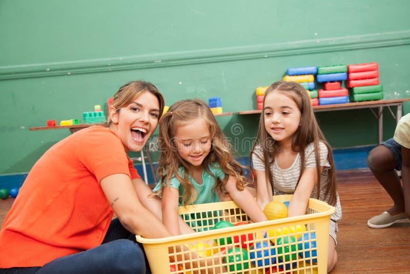 Leraar het spelen met haar kleuterschoolklasse royalty-vrije stock foto