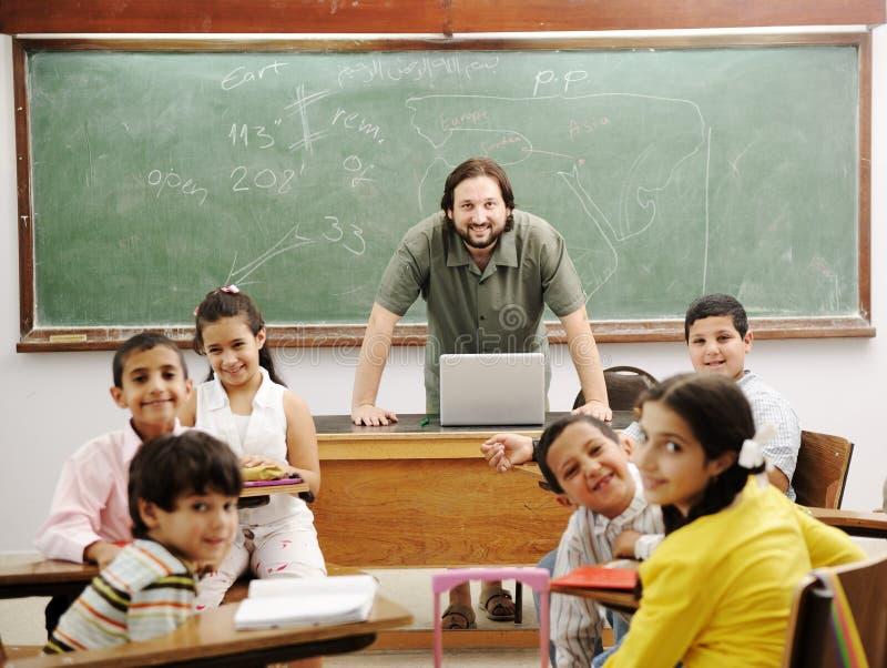 Leraar in klaslokaal met zijn kleine student stock fotografie