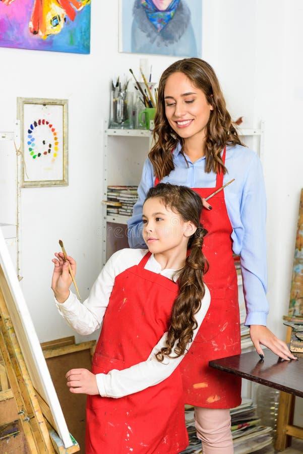 leraar letten die op hoe leerling het schilderen in workshop van stock foto's