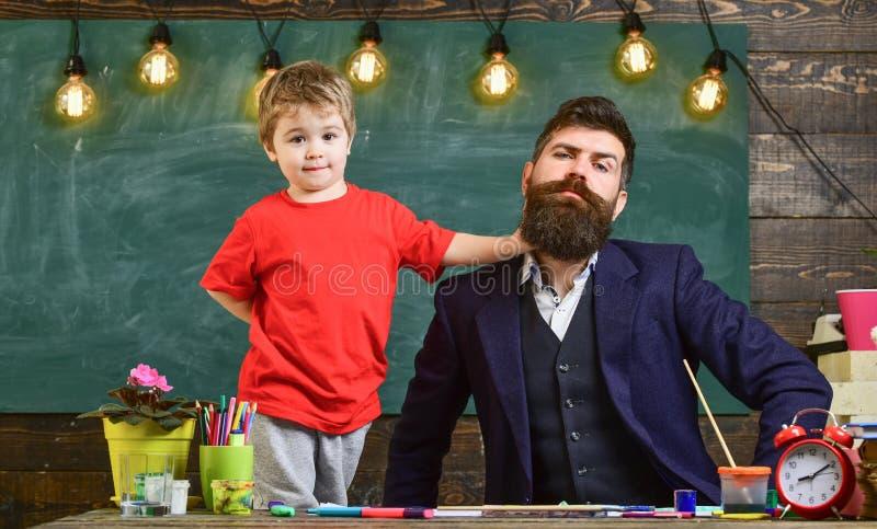 Leraar met baard, vader en weinig zoon die pret in klaslokaal, bord op achtergrond hebben Vrolijk kind en leraar stock afbeeldingen