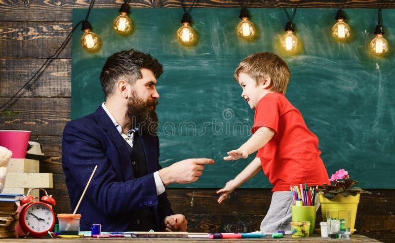 Leraar met baard, vader en weinig zoon die pret in klaslokaal, bord op achtergrond hebben Vrolijk kind en leraar royalty-vrije stock afbeelding