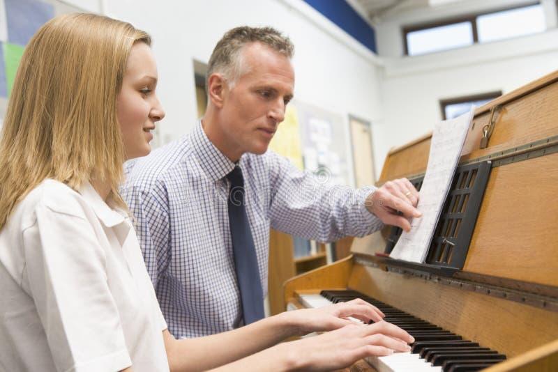 Leraar met schoolmeisje het spelen piano stock fotografie