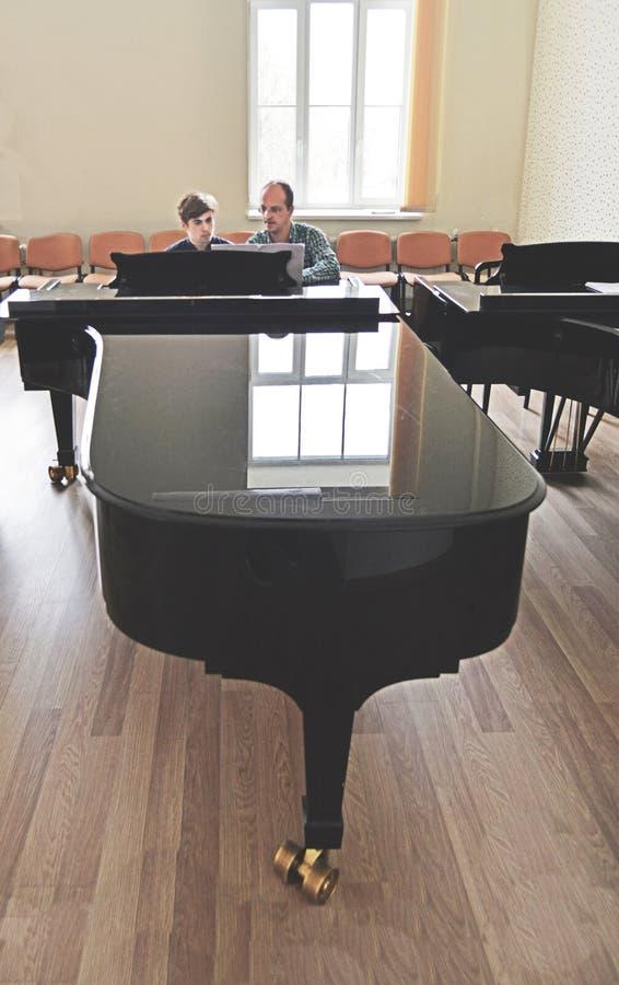 Leraar met student het spelen piano stock fotografie