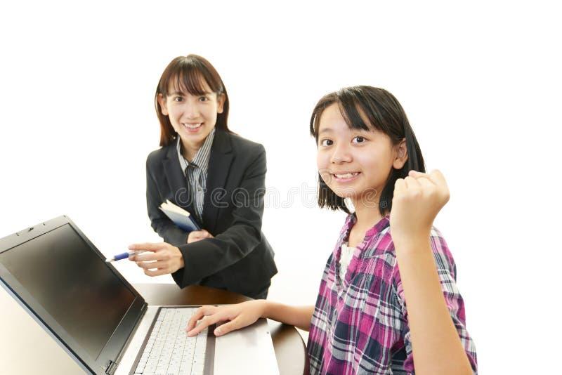 Leraar met tienermeisje het bestuderen. stock foto's