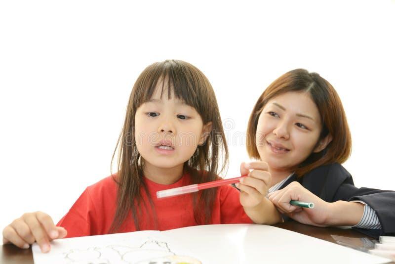 Leraar met tienermeisje het bestuderen. stock foto