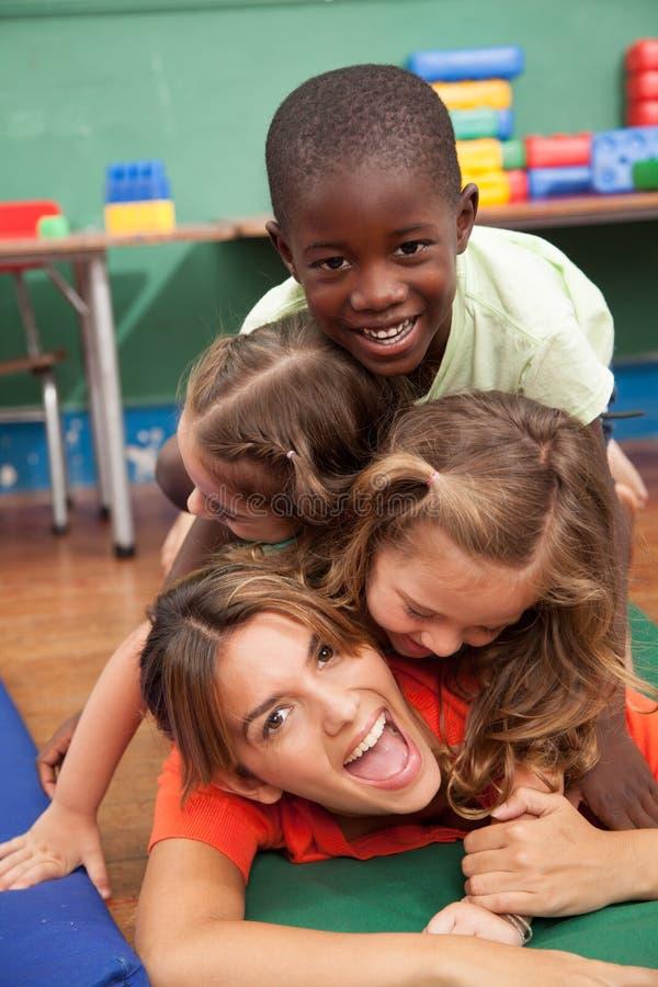 Leraar met van haar studenten die op de vloer spelen royalty-vrije stock foto